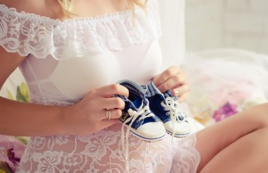 Pregnant holding booties