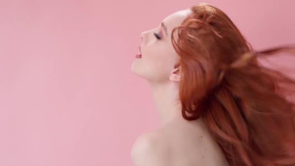 Krásná módní dívka s dlouhými kudrnatými zrzavými vlasy. Dívka ve studiu na růžovém pozadí. Reklama, vlasové výrobky, kosmetika, kosmetika, oblečení. Móda, butik. Růžová.