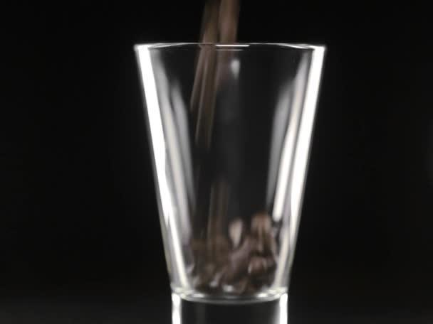 Kávová zrna jsou klesá do průhledného skla