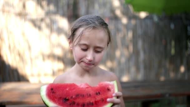 Happy little girl eating watermelon