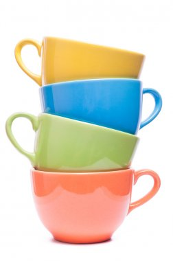 Four cups stacked. Colored mugs. Colorful image with tableware.