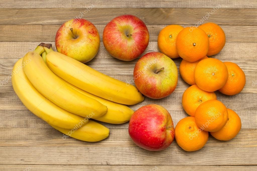 Groupe de bananes aux pommes et de mandarines sur bois — Photo
