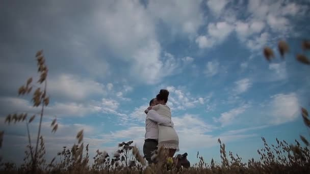 Loving couple whirls in a field on the sky background