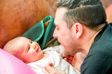 Dad makes faces grimacing newborn baby laughs
