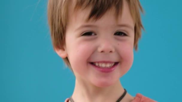 Malý chlapec v oranžovém tričku úsměvy na tyrkysovém pozadí