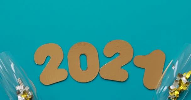 Čísla 2021 na modrém pozadí s sklenicemi šampaňského a cukroví