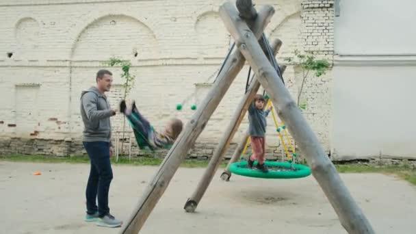 Otec třese dětmi na houpačce venku