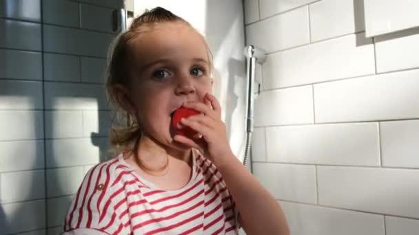 Little preschooler girl with fair hair licks yoghurt cap