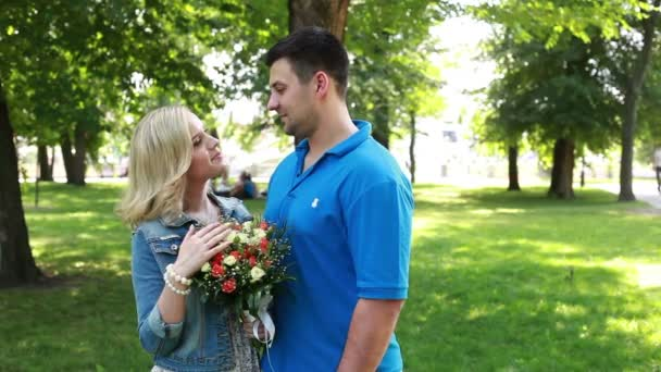 Female with bouquet kissing her male in summer park