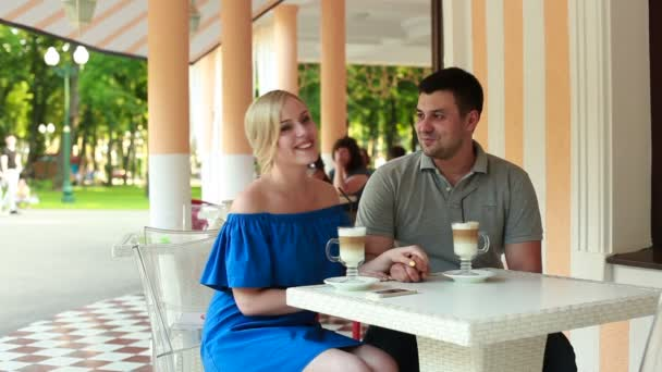 Couple in love talking and kissing in summer cafe