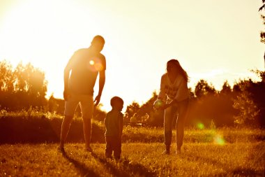 Happy family, father, mother, son and in nature, sunset.