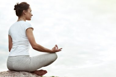 Yoga girl making a dzen or zen and smilling.