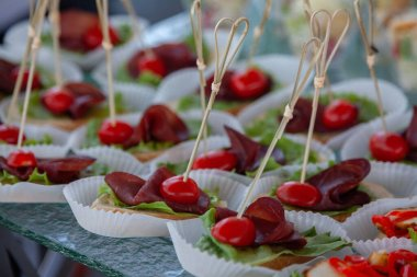 appetizer on skewers of meat, cherry tomatoes, lettuce and white bread