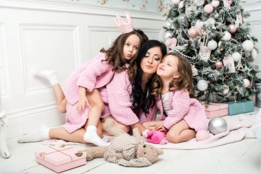 Young woman with two girls near the Christmas tree