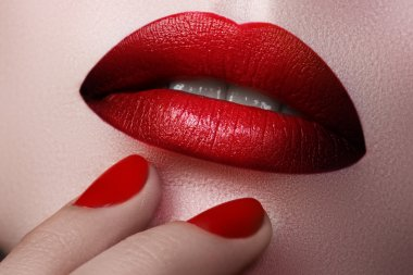 Close-up of woman's lips with fashion make-up and manicure. Beautiful female full lips with perfect makeup. Fashion visage. Part of female face. Macro shot of beautiful make up on full lips