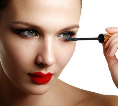 Mascara applying closeup, long lashes. Mascara brush. Eyelashes extensions. Make-up for blue eyes. Eye make up apply. Young beautiful woman applying mascara makeup on eyes by brush