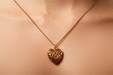 Golden heart pendant. Beauty and jewelry concept. Woman wearing shiny gold pendant. Fashion portrait of beautiful luxury woman with jewelry. Gift for Valentines day