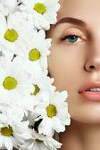 krása tvář mladé krásné ženy s květinou