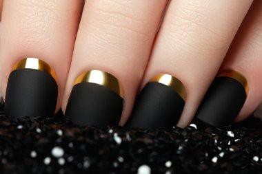 Manicure. Black matte nail polish. Manicured nail with black matte nail polish. Manicure with dark nailpolish. Golden nail art manicure. Holiday style bright manicure