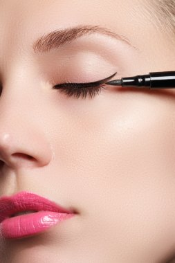 Beautiful woman with bright make up eye with sexy black liner makeup. Fashion arrow shape. Chic evening make-up. Makeup beauty with brush eye liner on pretty woman face