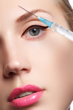 Closeup of beautiful woman gets injection. Full lips. Beautiful face and the syringe (plastic surgery and cosmetic injection concept).