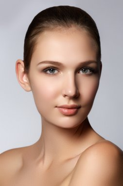 Glamour portrait of beautiful woman model with fresh daily makeup. Fashion shiny highlighter on skin, sexy gloss lips make-up and perfect eyebrows. Natural beauty