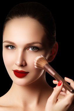 Make-up and cosmetics. Beauty woman face isolated on black background. Beautiful model girl makeup. Gorgeous lady with blue eyes and brown hair. Perfect skin. Professional make up. Red lips
