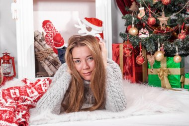 Charming girl in a Christmas interior with tree