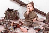 Kind auf weißem Hintergrund mit Militärspielzeug