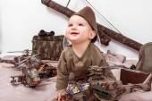 Fotografie Kind auf einen weißen Hintergrund mit militärischen Spielzeug