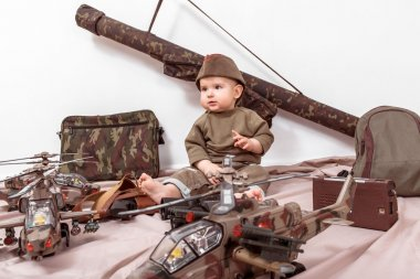 child on a white background with military toys