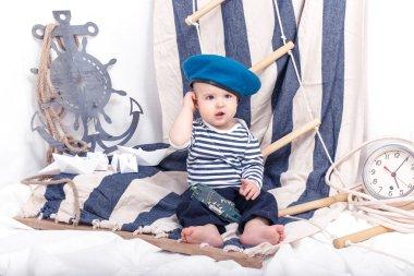 A small child in a sailor sea interior with paper boats