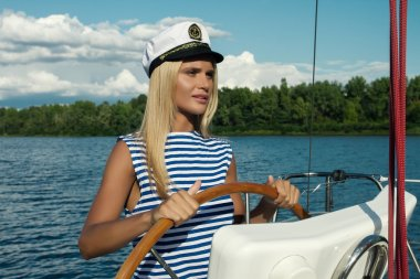 Beautiful young blonde woman at helm of ship