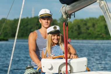 Young couple man and woman sailors at the helm of yacht.