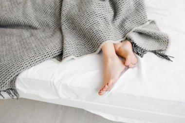 Female legs under grey blanket