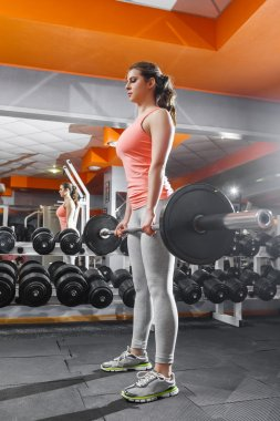 Sportswoman lifting hard barbell at gym
