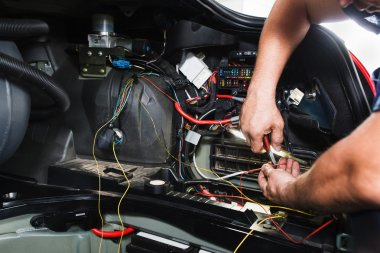 Electrician works with electric block in car
