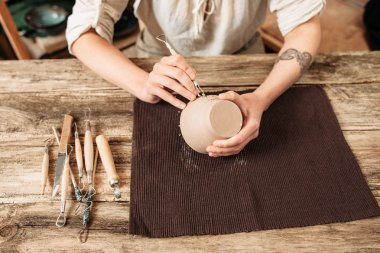 Clay bowl author decorating, pottery making