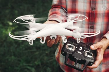 Operator holding remote control and quadrocopter