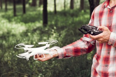 Unrecognizable man running drone in forest