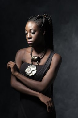 beautiful  thoughtful Black woman with an ethnic necklace