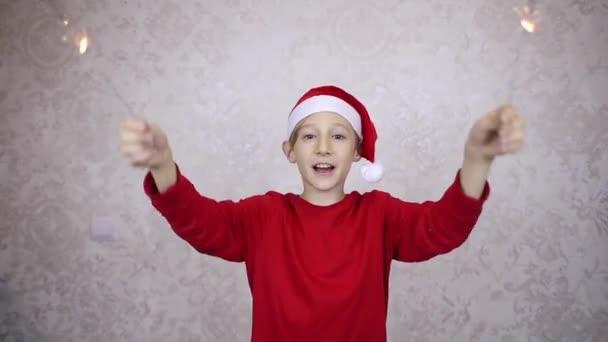chlapec s červeným kloboukem Santa a jiskry přeje šťastný nový rok