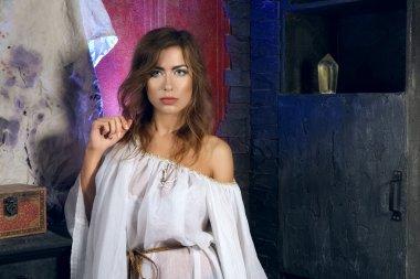 Pretty mystic lady in gothic white dress in underground dungeon