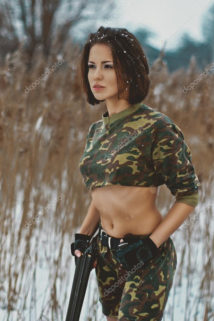 pretty girl in camouflage with rifle