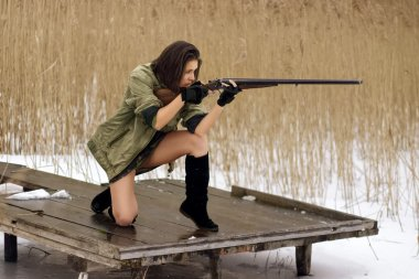 pretty girl shooting duck with double barrel rifle