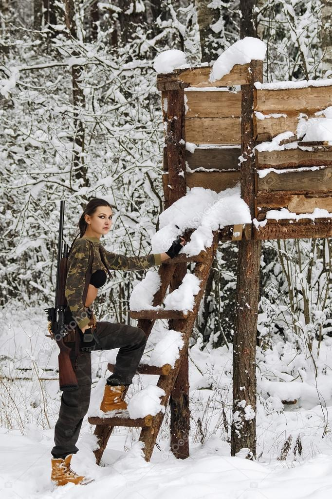 attractive hunter girl with rifle on hunting tower in winter for