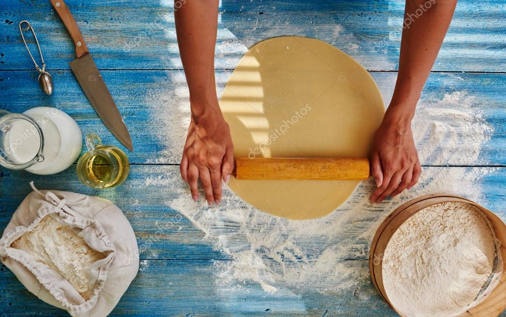 The bakery woman chef rolls the dough with a rolling pin