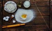 Cook broke an egg into the flour to make a dough