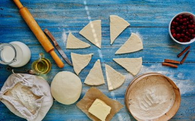 On the wooden kitchen table is sliced dough