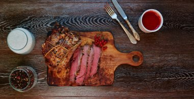 On the table is a wooden board on which the chef cut a piece of meat into portions